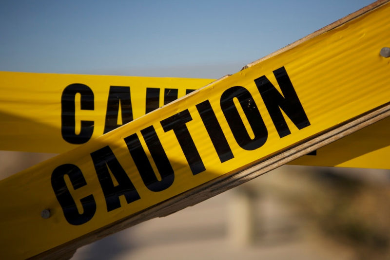 Close-up photo of police-style caution tape stretched across an out-of-focus background.