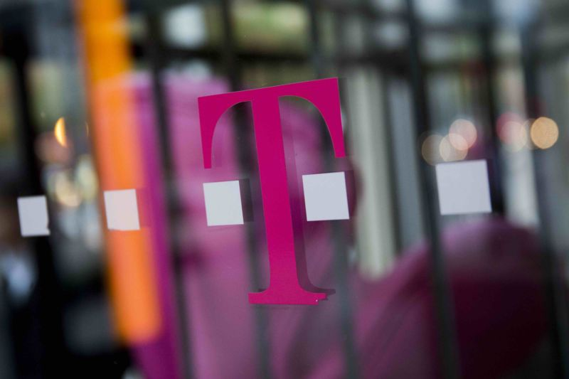 A T-Mobile logo on the window of a retail store.