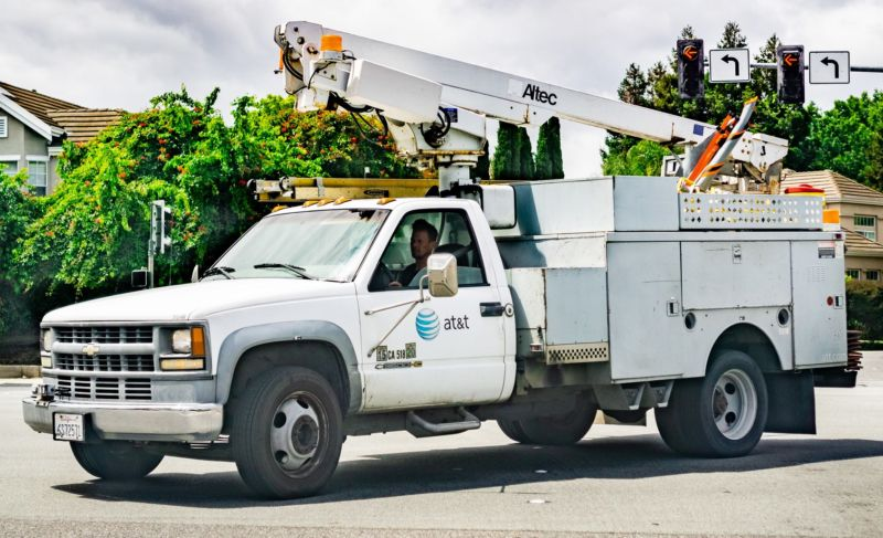 AT&T service truck driving on a street in a residential neighborhood.