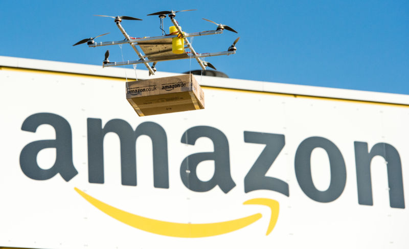A drone with an Amazon package floats in front of the Amazon logistics center in Leipzig, Germany, 28 October 2014. Amazon did not comment on whether drones will fuel this default one-day speed boost for paying Amazon Prime subscribers' deliveries.