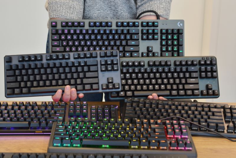A person whose head is cropped from the photo poses with 6 computer keyboards.