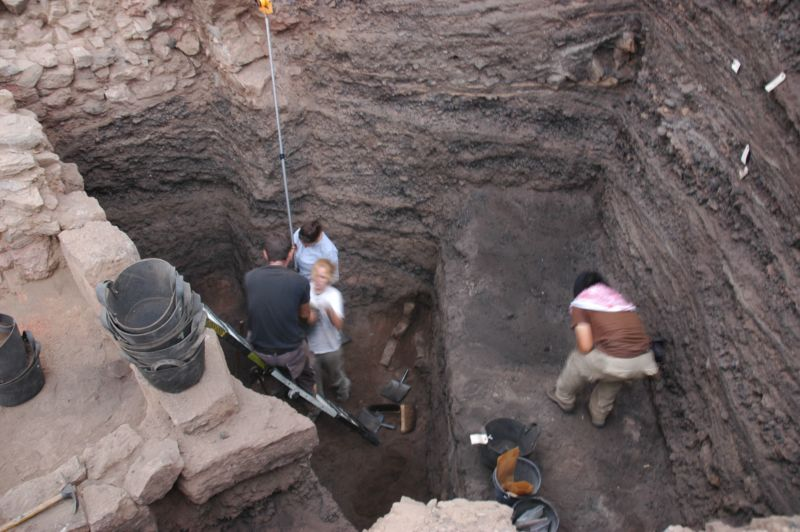Color photo of archaeologists excavating layers of copper production waste in a deep pit.