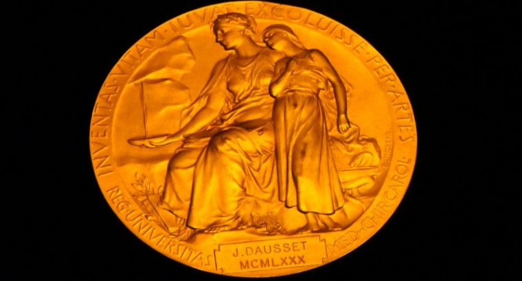Ornate gold medal on black background.