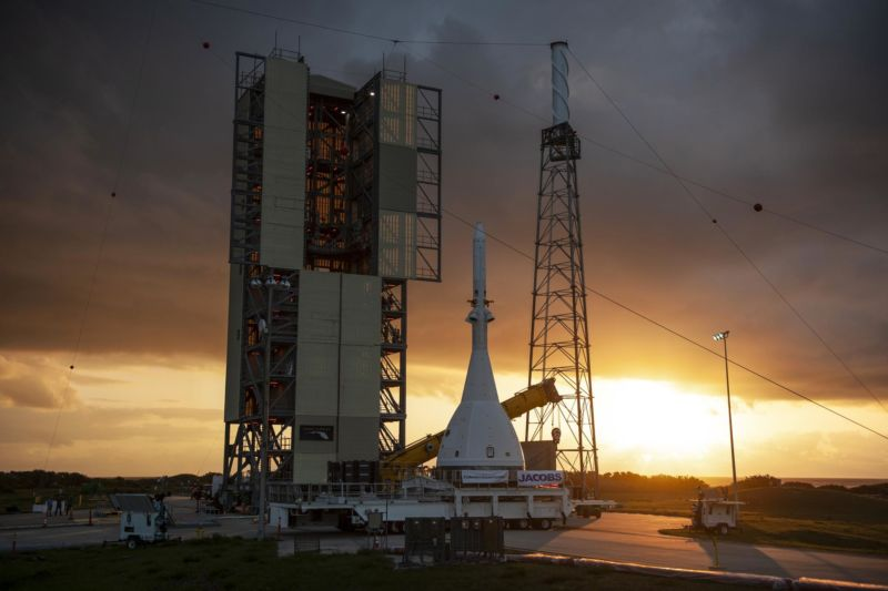A rocket sits on a launch pad at dawn.