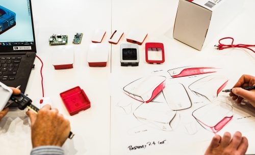 Top-down photo of a desk covered with white paper on which are a couple of Raspberry Pis and several cases. The hands of someone sketching red and white cases on the paper are visible. Also visible are the hands of someone measuring something with digital calipers, beside a laptop on the screen of which is a CAD model of a Raspberry Pi case.