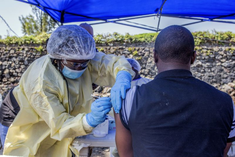 A nurse in PPE administers a shot to a man in an outdoor clinic.