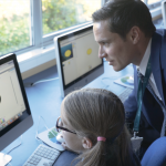 Male teacher and female student at a computer