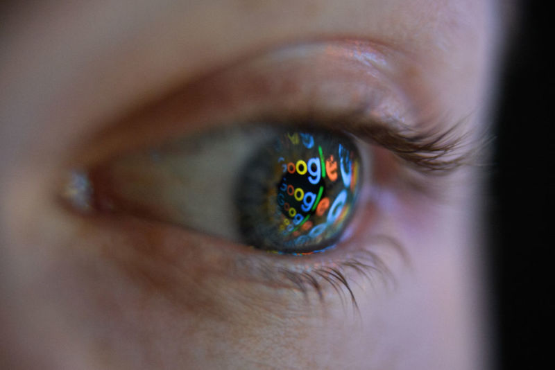 Photo illustration showing the Google logo reflected on the eye of a young man.