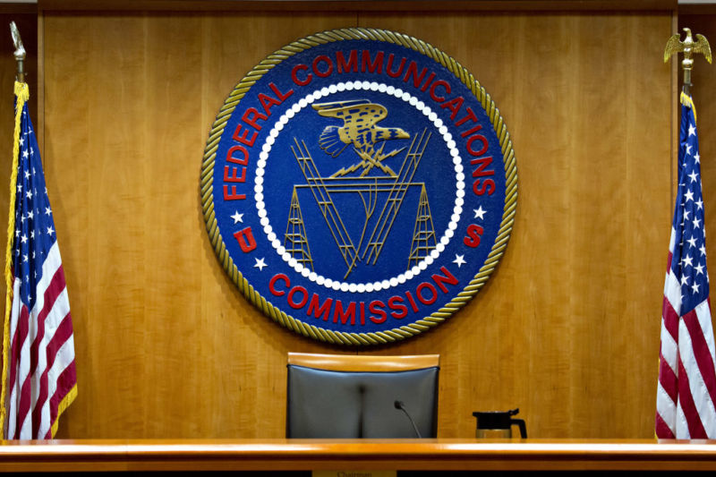 The Federal Communications Commission meeting room, with an empty chair in front of the FCC seal and two United States flags.