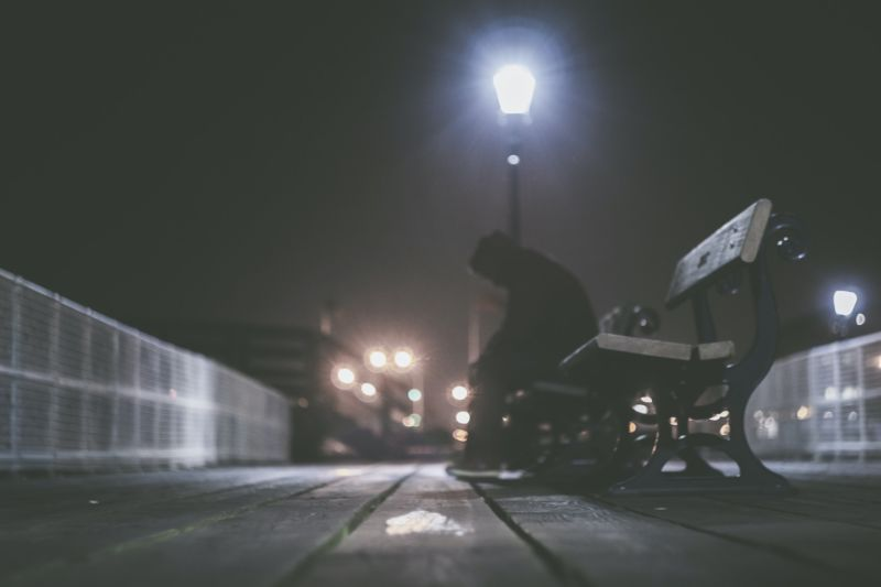 A lonely person sitting on a bench at night.