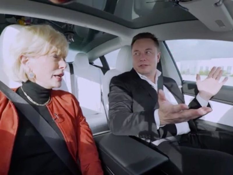 Elon Musk and Barbara Walters in a Tesla. Musk has his hands off the steering wheel as the car is driving.