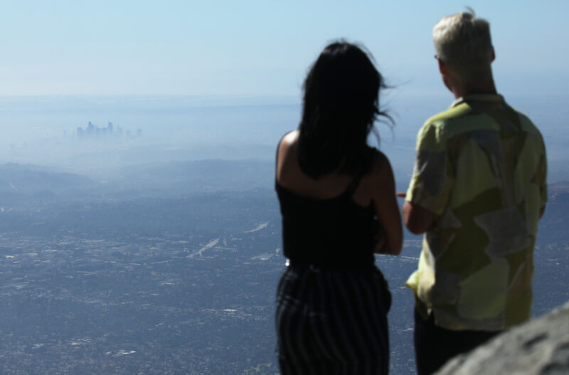 A man and a woman, properly socially distanced from the rest of Los Angeles, take in a view of the city on a low air quality day in November, 2019.