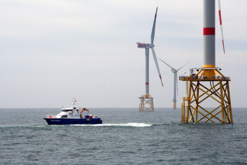 Image of a boat near the base of an offshore wind farm.
