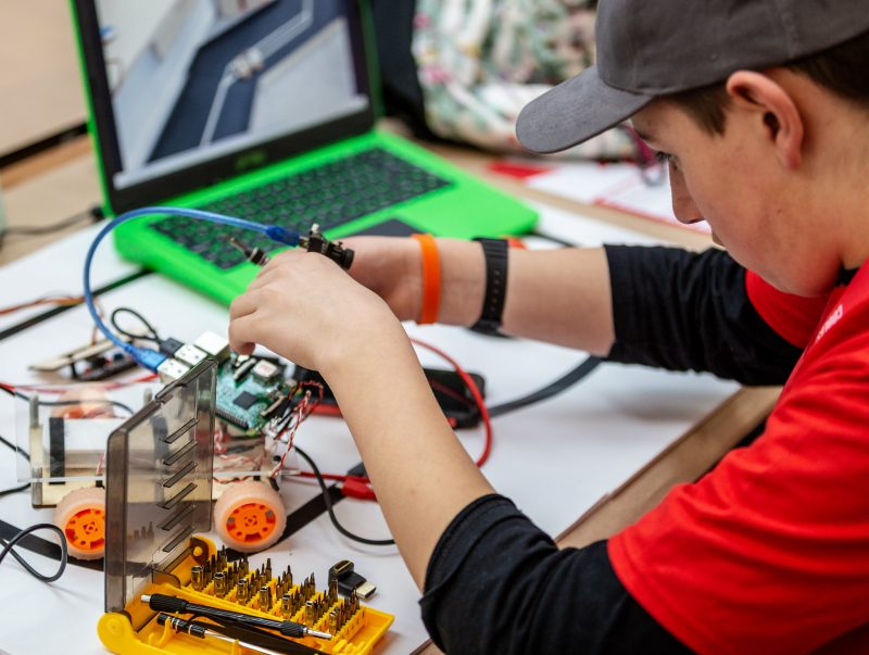 A boy working on a Raspberry Pi robot buggy