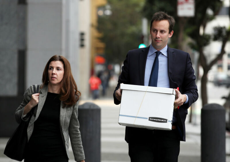 Anthony Levandowski walking to a courthouse while holding a cardboard box.