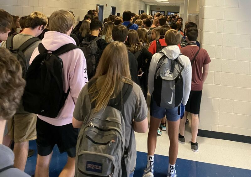 A photo of high school students in a hallway between classes, with kids packed closely together and many not wearing masks.