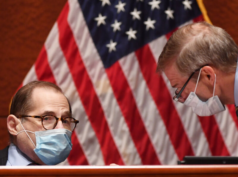 Two men in suits and face masks confer in front of a US flag.
