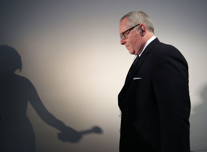 The shadow of a reporter with a microphone falls on the wall behind a man in a suit.