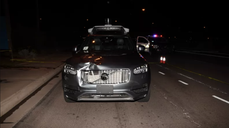 A silver SUV with a damage grill is parked on a street at night.