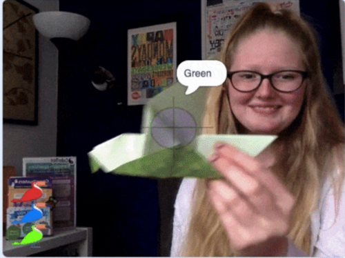Photo of a young woman holding an origami bird up to the camera