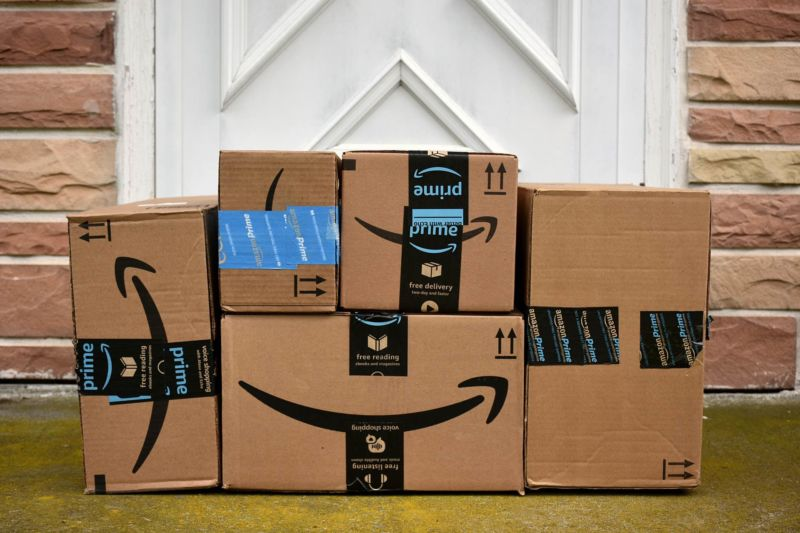 A pile of Amazon boxes in front of the door of a house.