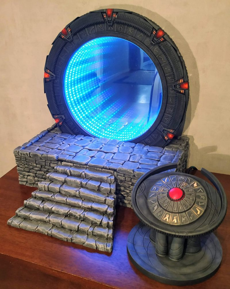 A mini version of the Stargate from TV sat on a table. Blue glowing light emits from the fake tunnel