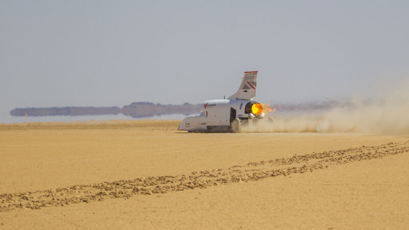 A rocket-propelled car screams across the desert.