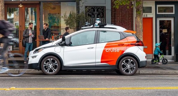 A white and red self-driving car parked on a street in San Francisco