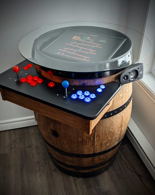 A beer barrel with drinks inside two opening doors cut into the front of the barrel and a retro arcade console serving as the lid of the barrel with joystick and buttons on a ledge in front