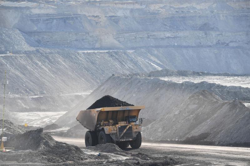 Dumptruck full of coal drives through strip mining area.