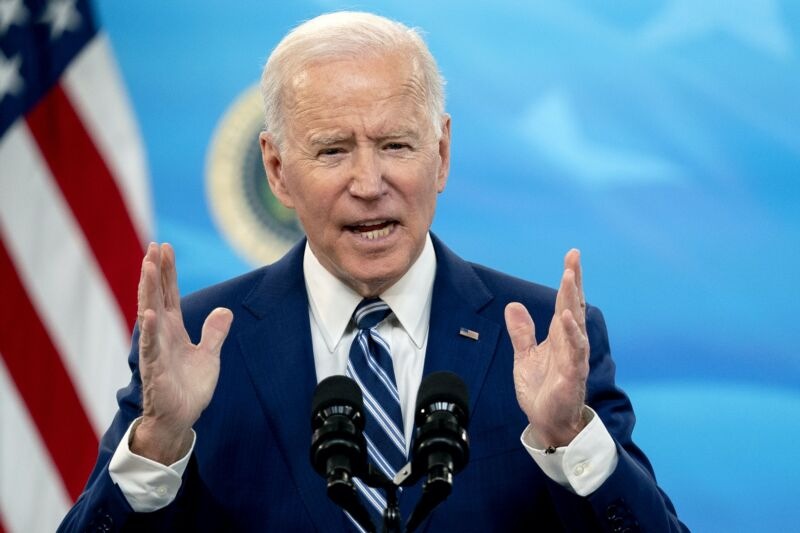 President Joe Biden speaking into a microphone and gesturing with his hands.