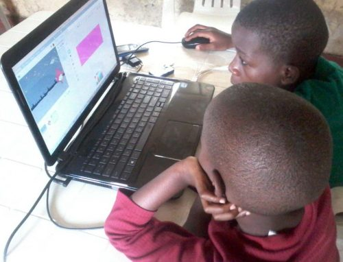 Two young children code in Scratch on a laptop.