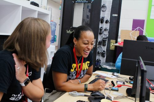 A teacher attending Picademy teacher training laughs as she works through an activity.