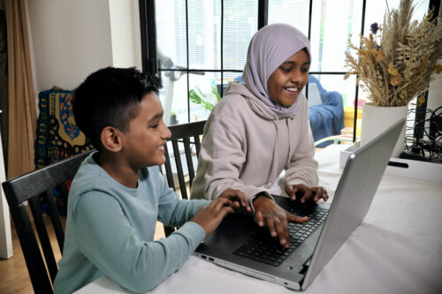 A sister and brother smiling while doing digital making at a laptop