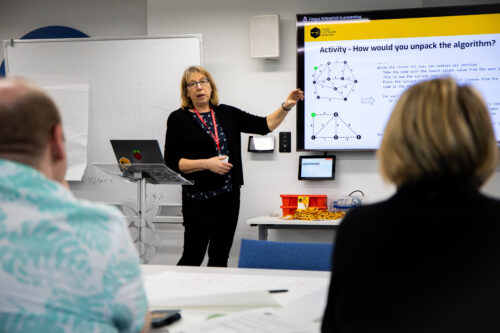 A woman teacher presents to an audience in a classroom.
