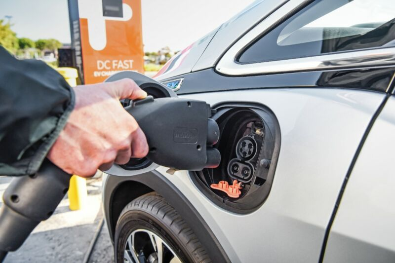 Someone about to plug a DC fast charger into a Chevrolet Bolt EV.