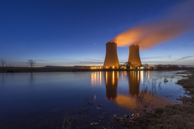 Image of two cooling towers above a body of water.