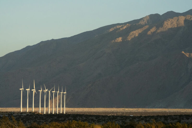 A wide angle shot of wind turbines at the foot of a mountain.