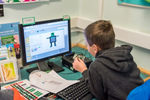 A child codes at a desktop computer.