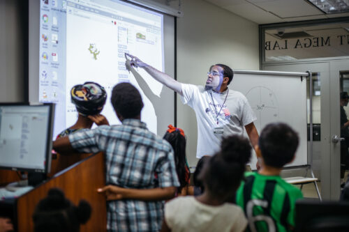 A mentor explains Scratch code using a projector in a coding club session.