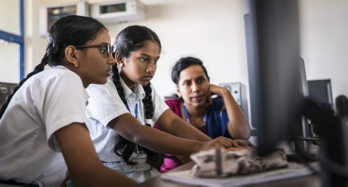Two girls code at a desktop computer while a female mentor observes them.