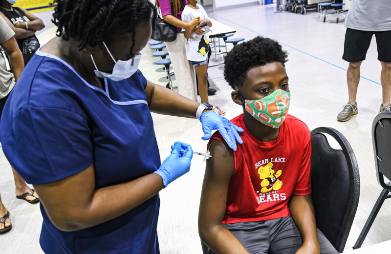 A nurse gives a boy a dose of the Pfizer vaccine at a COVID-19 vaccine clinic in Florida on the day before classes begin for the 2021-22 school year.