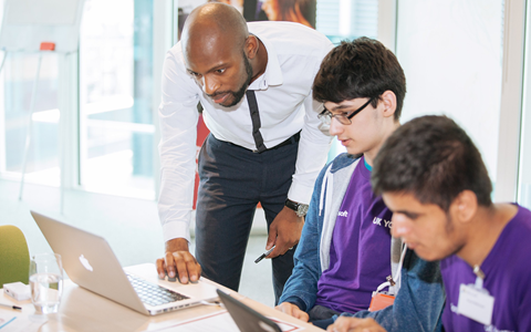 An educator helps a young person with a computing problem.