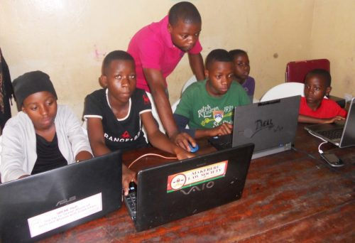 A man helps four young people to code projects at laptops in a CoderDojo session.