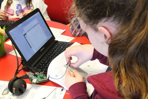 A girl doing a physical computing project with Raspberry Pi hardware.