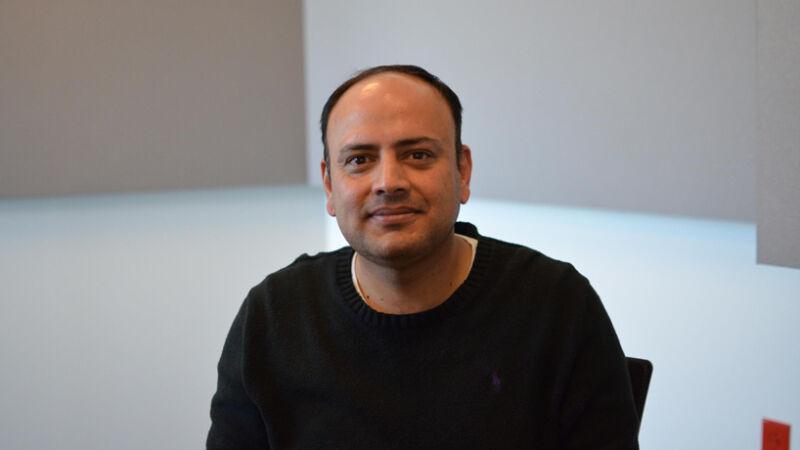 Cybersecurity professor Shaji Khan sitting in a chair.